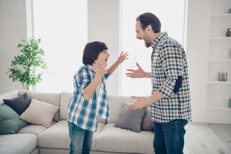 Profile side view portrait of two nice mad pissed off guys dad and pre-teen son in casual checked shirt having big fight disagreement behavior in light white modern style interior living-room Banque d'images