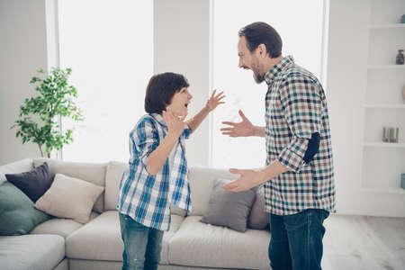 Vue latérale du profil portrait de deux gentils gars fous énervés papa et fils pré-adolescent en chemise à carreaux décontractée ayant un grand comportement de désaccord de combat dans un salon intérieur de style moderne blanc clair