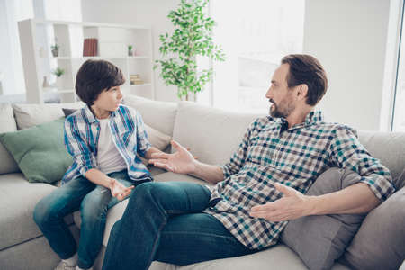 Portrait of two nice attractive friendly guys dad and pre-teen son sitting on couch discussing psychology generation problems in light white modern style interior living-room Foto de archivo