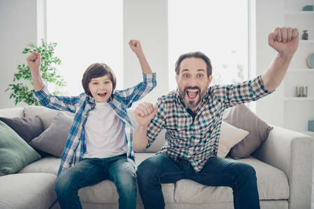 Portrait of two nice attractive cheerful cheery glad guys dad and son watching sports on TV having fun at light white modern style interior house living-room indoors
