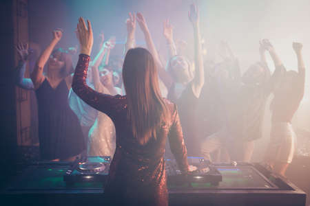 Rear back behind view of dj performing stereo sound rhythm trance techno, electronic style music for stylish cheery crowd enjoying event concert having fun bachelor at fashionable modern nightclub