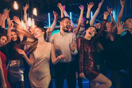 Photo of excited crazy cheerful overjoyed corporate people dressed in formalwear celebrating his friend birthday singing screaming shouting dancing under lights of neon