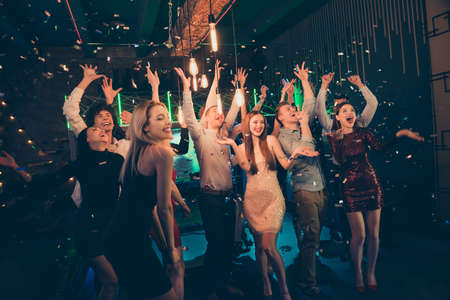 Photo of screaming cheerful excited ecstatic beautiful company dressed in formalwear chilling out at night club catching confetti with smiles on their faces