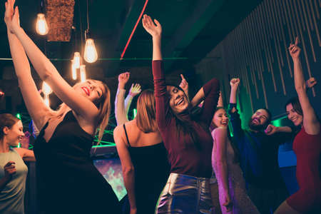 Portrait of delighted girl company corporate visit with group buddies party nightclub on her birthday anniversary raise hands have fun dance wear formalwear dress skirt in discotheque