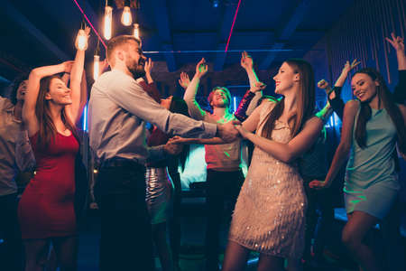 Lets dance my love. Portrait of positive cheerful couple students have wedding party dance on discotheque with lots people crowd wearing formalwear dress skirt in spotlight Фото со стока