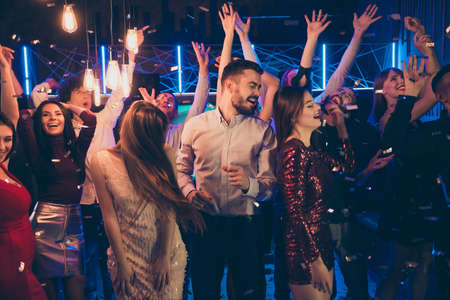 Photo of cheerful attractive beautiful students dressed in formalwear celebrating brithday of his friend surrounded by girls feeling carefree washed with neon light turned by dj