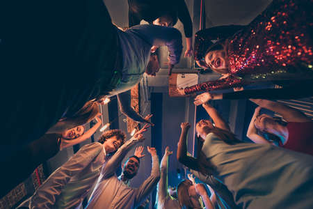 Low angle view photo of cheerful positive wild group people stand around having fun on party dance feel rejoice crazy raise hands wear formalwear dress shirt on discotheque