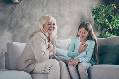 Foto von fröhlichen, positiv humorvollen, freundlichen Verwandten, die zusammen lachen und eine Geschichte erzählen, die Oma scherzt über ihre Jugendzeit, die auf dem Sofa sitzt