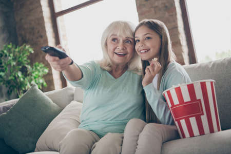 Photo of two people aged white haired granny small granddaughter sit cozy sofa watching tv eat popcorn spending summer weekend holidays together house indoors