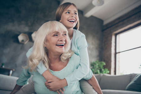 Low angle view photo of two best friends people cute aged granny small grandchild girl hug piggyback playing funny game spend weekend together house indoors Stok Fotoğraf