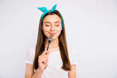 Portrait of inspired dreamy girl hold fork feel hungry want eat imagine tasty meal delicious burger close eyes wear stylish blue headband t-shirt isolated over white color background