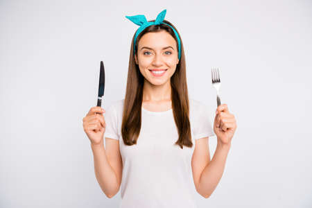 Close-up portrait of her she nice attractive lovely charming winsome cheerful cheery girl holding in hands fork knife crockery isolated over light white color background Stock fotó