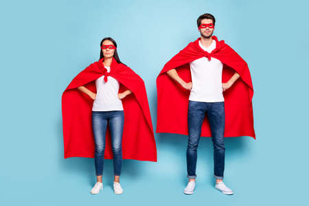 Full length body size view of his he her she nice attractive content serious couple wearing red superhero outfit hands on hips isolated on bright vivid shine vibrant blue turquoise background