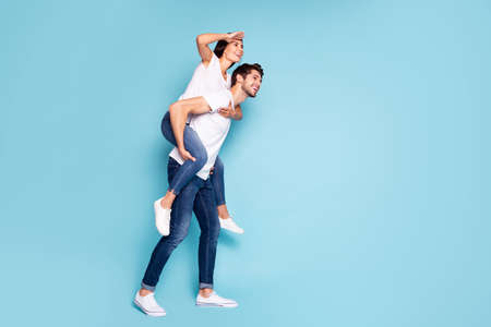 Full length body size profile side view of nice attractive cheerful dreamy couple piggybacking having fun looking watching vacation isolated on bright vivid shine vibrant blue turquoise background Stok Fotoğraf