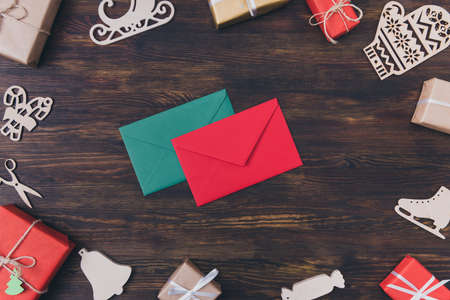 Writing letter to Father Christmas from child concept. Top above high angle view photo of two colorful vivid paper envelopes surrounded by different noel eve stuff wrapped giftboxes