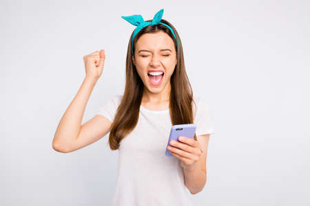 Portrait of positive cheerful girl use her cellphone get notification about victory in online lottery raise fists scream yeah wear retro style clothes isolated over white color background