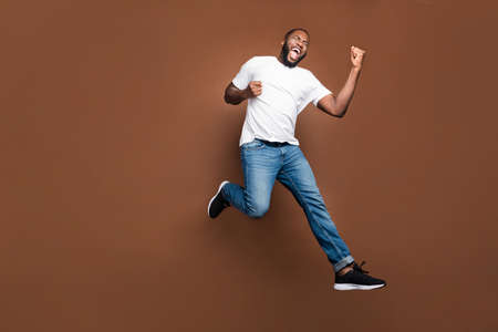 Full length body size photo of cheerful positive excited crazy ecstatic overjoyed man rejoicing about having bought new discounted jeans denim footwear white t-shirt jumping running isolated pastel color background