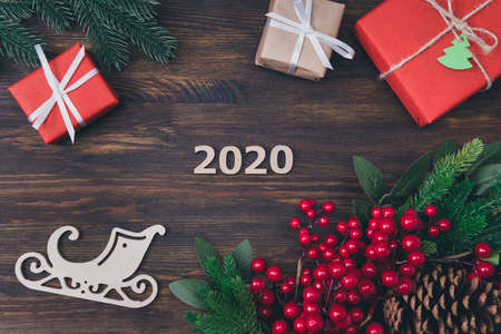 2020 is coming. Top above high angle view photo of 2020 numbers small and big giftboxes with white ribbon pine cones with red berries on darn wooden background 스톡 콘텐츠