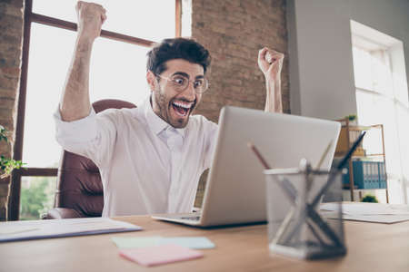 Portrait of crazy surprised middle eastern businessman indian marketer work on computer got notification about successful win project scream yes raise fists sit desktop in loft workstation Stock Photo