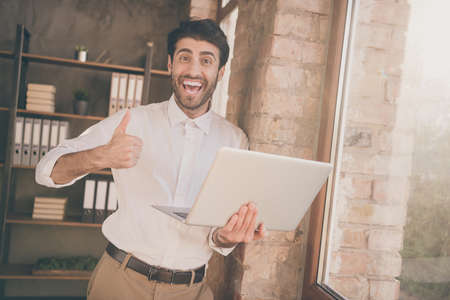 Portrait of positive indian businessman lawyer hold use laptop approve new effective seminar workshop great teamworking training show thumb up wear white shirt pants in loft company office workplace Stock Photo