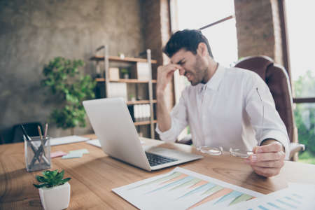 Profile side photo of exhausted middle eastern entrepreneur have lots work on computer touch his nose hold glasses feel burnout sit desk in loft wearing white shirt