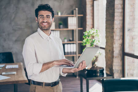 Portrait of confident indian business agent holding laptop typing email feel positive want self-development on work stand in loft enterprise office