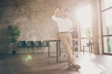 Full size photo of ecstatic indian freelancer having glasses feeling smart get sms about new partners start-up deal scream yes raise fists wear white shirt pants trousers stand in loft workplace Stock Photo
