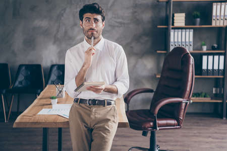 Portrait of hesitating indian collar hold copybook want plan his daily routine work tasks stand near table wearing white shirt in loft enterprise company