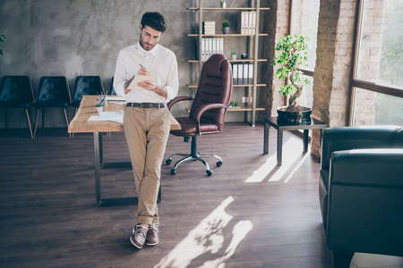 Full length photo of concentrated serious middle eastern businessman write in copybook make plans managing stand near table in loft company office Stock Photo