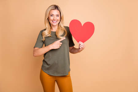 Photo of cheerful positive cute nice pretty sweet girlfriend smiling toothily wearing green t-shirt yellow pants trousers pointing at red heart boasting about it near empty space isolated pastel beige color background