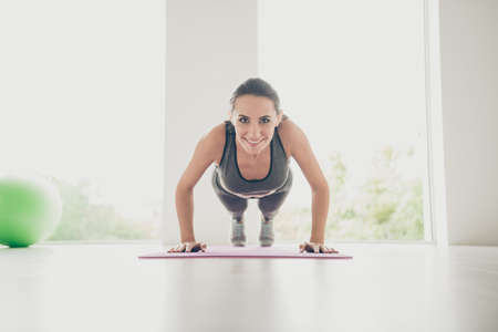 Full body photo of sportive positive woman doing plank exercise feel energy stretch her elbows like feelings of motivation wear sport wear pants in house like gym indoors