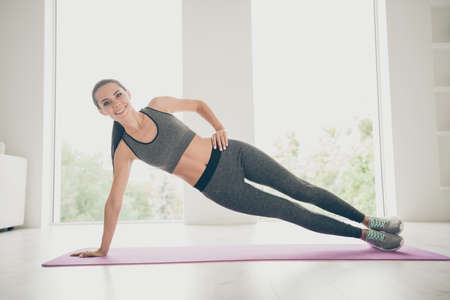 Full body photo of sporty girl having sport wear pants practice in her home house gym-like studio stretch legs arms