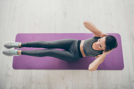 Top above high angle view photo of cheerful positive sport girlfriend wearing sportswear doing crunches indoors on carpet floor Banco de Imagens
