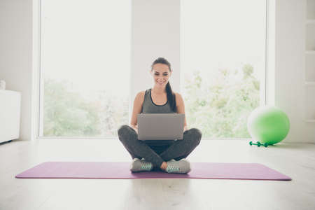 Full body photo of positive sportive girl crossing her legs sit on violet mat use laptop browse films movie about sport practicing in gym like house indoors