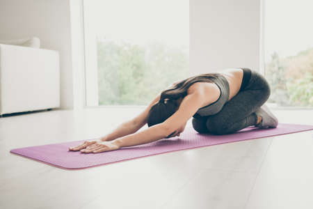 Full body photo of concentrated motivated girl sit on floor purple mat stretching her arms leaning want be strong physically fit woman wearing modern stylish pants clothes in gym like house Stok Fotoğraf