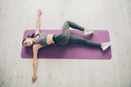 Top above high angle photo of sportive woman lie on purple mat doing gymnastics, exercise follow regime to become slim beauty in home house gym Stock Photo