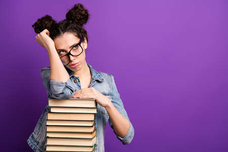 Photo of pretty student lady leaning on many books tired of boring lesson want go home wear specs casual denim outfit isolated purple color background Reklamní fotografie