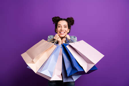 Portrait of positive cheerful girl have fun on shopping hold many bags packages feel content expression wear denim jeans jacket isolated over purple color background