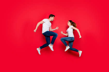 Side profile full body size photo of cheerful nice cute couple of girlfriend boyfriend bumping into each other smiling running jumping jeans denim white t-shirt isolated vivid color background Stockfoto - 133269029