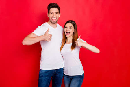 Photo of cheerful positive nice cute pretty couple of boyfirend and his soulmate showing you thumb up with jeans denim white t-shirt expressing emotions isolated vivid color red background