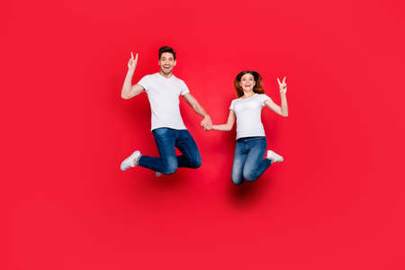 Full length body size photo of cheerful positive nice pretty couple of girlfriend boyfriend wearing jeans denim white t-shirt smiling toothily isolated vivid color background jumping showing v-sign Stockfoto - 133269205