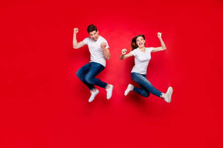 Full length body size photo of cheerful positive jumping excited rejoicing overjoyed girlfriend boyfriend wearing jeans denim white t-shirt footwear screaming yes yeah isolated vivid color background Stockfoto - 133269204