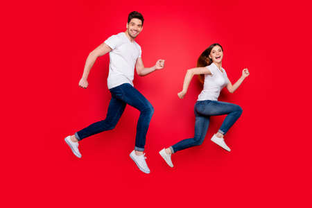 Side profile full length body size photo of cheerful positive nice pretty sweet couple of crazy spouses wear jeans denim white t-shirt smiling in footwear isolated vivid color background run jump
