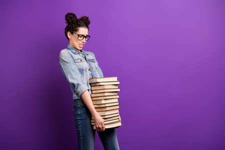 Profile photo of funny student lady holding many books need to study much carry literature home wear specs casual denim outfit isolated purple color background