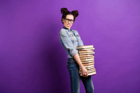 Profile photo of amazing student lady holding many books need to study much carry literature home wear specs casual denim outfit isolated purple color background Reklamní fotografie