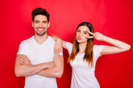 Photo of cheerful positive nice charming couple of girlfriend boyfriend wearing white t-shirt showing v-sign with hands folded smiling toothily isolated vivid color background