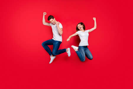 Full length body size photo of cheerful positive excited ecstatic overjoyed girlfriend wearing jeans denim white t-shirt footwear screaming yes yeah jumping isolated vivid color background Stockfoto - 133269244
