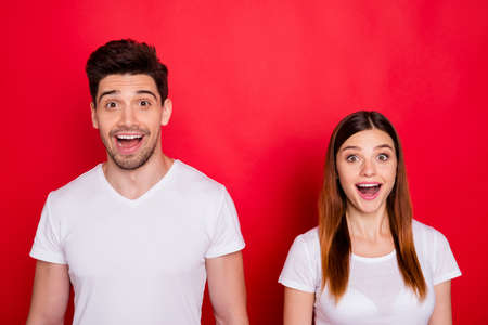 Photo of cheerful excited white t-shirt cute pretty sweet couple of spouses excited about discount at shopping center with emotions on faces isolated vivid color background