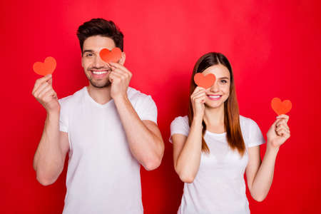 Photo of cheerful positive nice pretty couple of boyfriend girlfriend smiling toothily covering their eye showing their love with red heart white t-shirt postcards isolated vivid color background