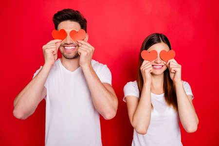 Photo of cheerful positive pretty nice couple of loving people covering their eyes with small hearts postcards smiling toothily isolated vivid color background wearing white t-shirt